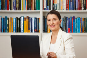 woman sitting in front of bookcase