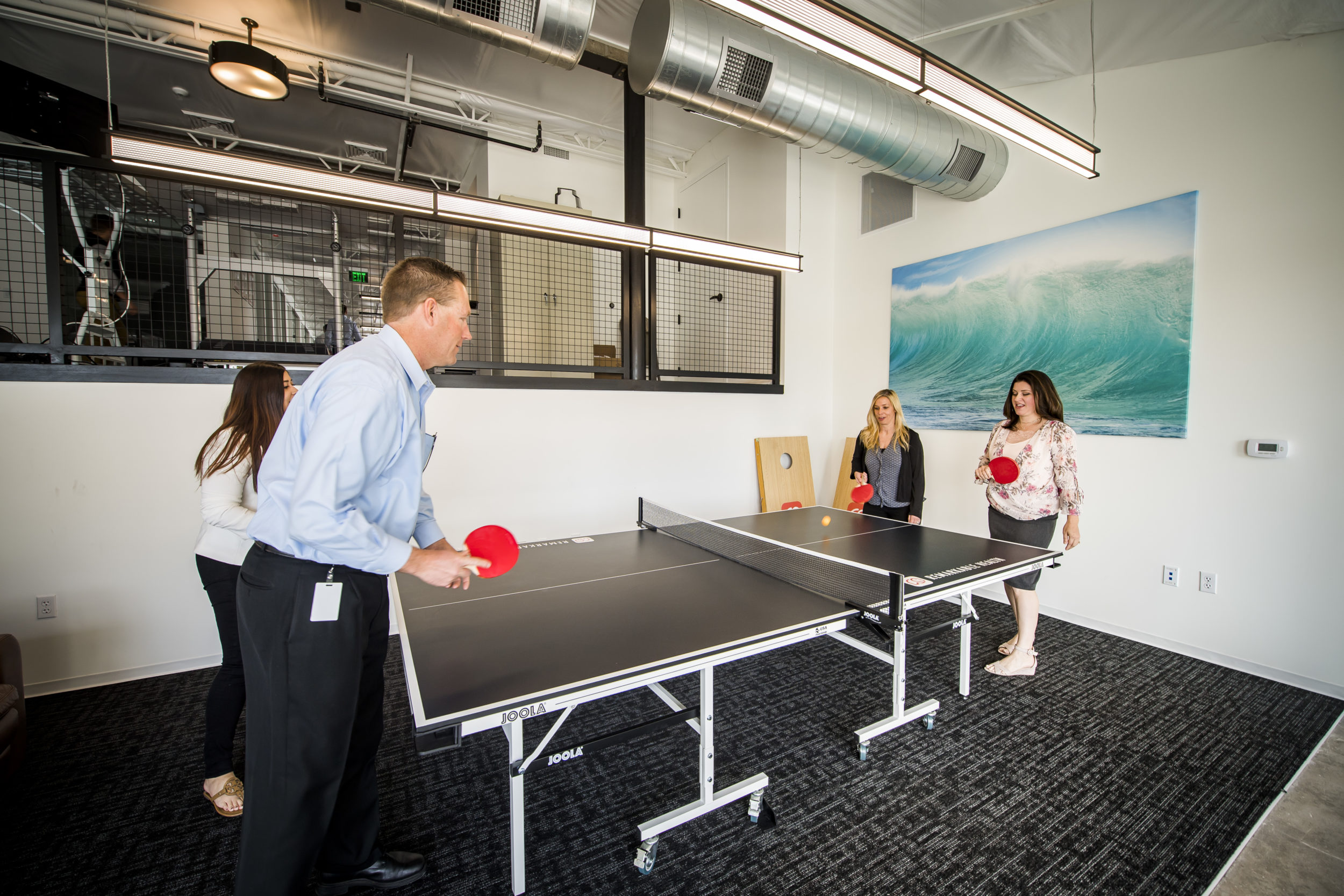 remarkable health employees playing ping pong during break