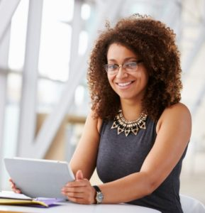 woman smiling while working on tablet