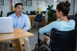 man interacting with woman in wheelchair
