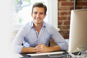 man smiling at computer