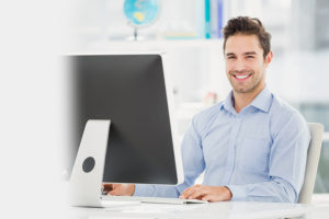 man smiling while at computer