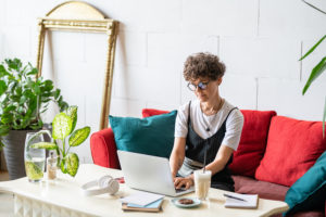 young home office manager sitting on couch with pillows in front of laptop